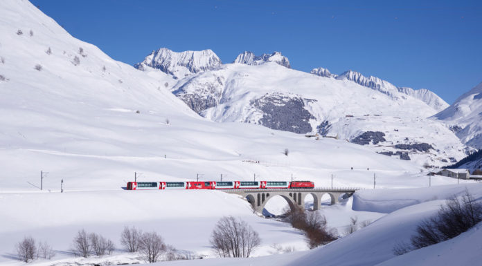 Glacier Express rolling past ski resorts in winter
