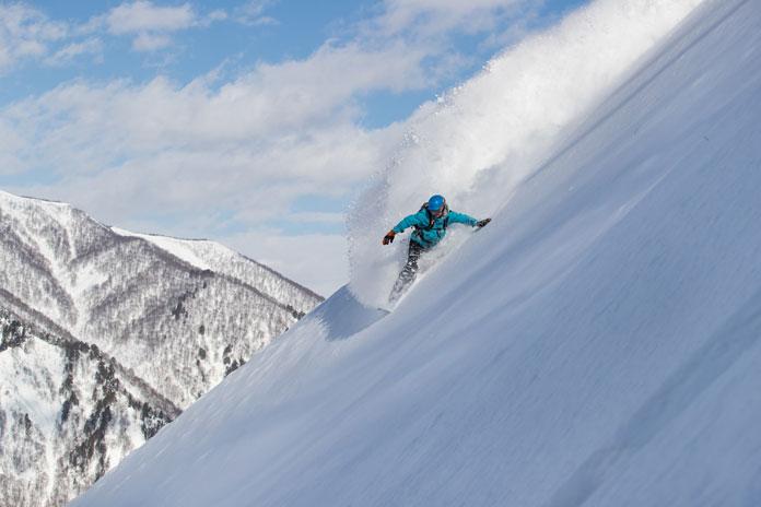 Snowboarded Adam Portland slashing a steep powder line at Tanigawadake Tenjindaira