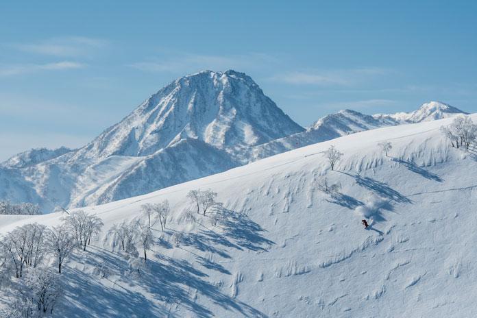 Skiing Lotte Arai Resort in-bounds off piste powder terrain with view to Mt Myoko