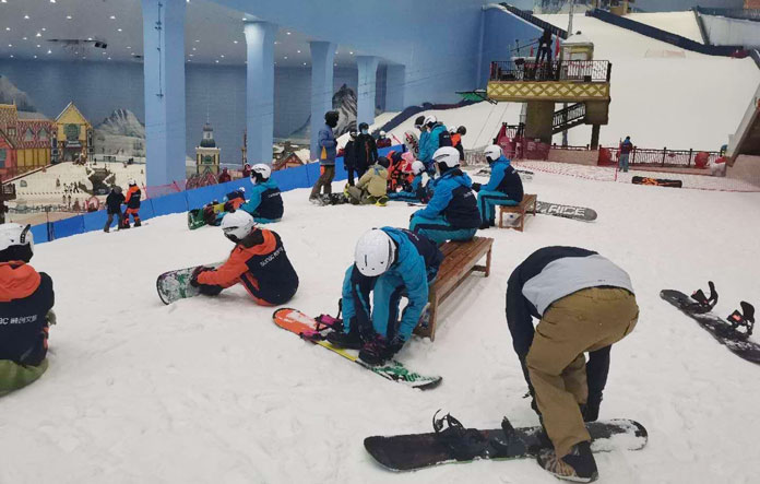 Snowboarders strapping in at Gunagzhou Sumac Snow PArk