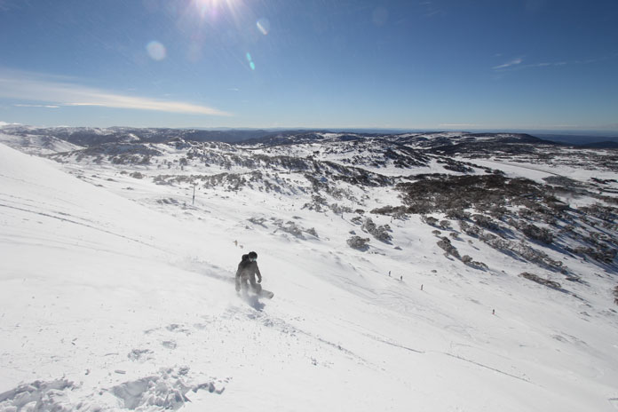 Snowboarder slashing boot deep snow on Olympic at Perisher