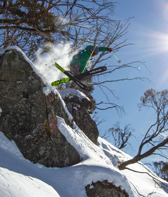Skier leaping off boulder Mount Wheatley Perisher
