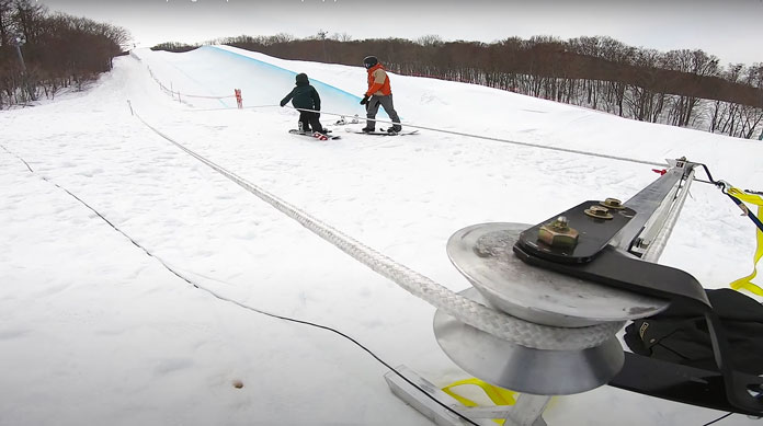 View of Towpro portable rope tow with anchor station set at bottom of slope
