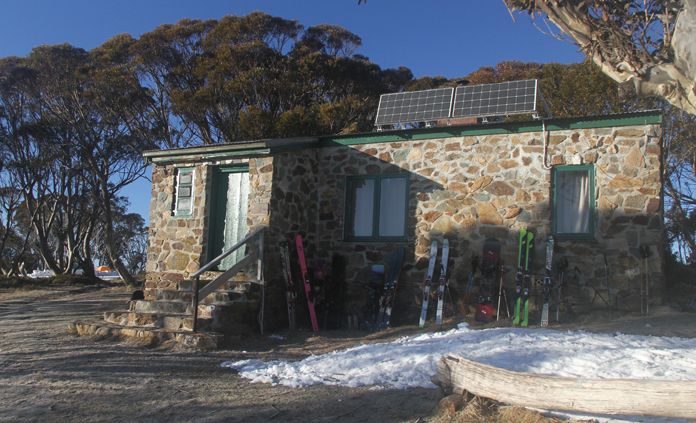 Exterior view of Cleve Cole hut in spring with skis outside